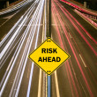 """RISK AHEAD"" sign against highway trails - Stock Photo"