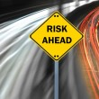 """RISK AHEAD"" sign against highway trails — Stock Photo #18466271"