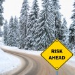 """RISK AHEAD"" sign against winter road — Stock Photo"