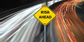 """RISK AHEAD"" sign against highway trails — Stock Photo"