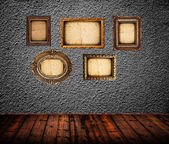Empty room interior with black wall and vintage photo frames — Stock Photo