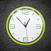 Green retro clock on black grunge wal — Stock Photo