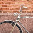 Bicycle against brick wall detail — Stock Photo