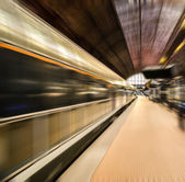 Train station and train in motion blur — Stock Photo