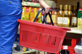 Hand holding empty shopping basket - Shopping concept — Stok fotoğraf