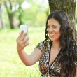 Beautiful teenage girl having a video call outdoors - Stock Photo