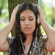 Beautiful woman enjoying music outdoors - Stock Photo