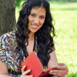 Portrait of beautiful girl reading book outdoors — Stok Fotoğraf #24703133