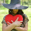 Portrait of girl holding big red heart outdoors — Stock Photo