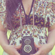 Retro image of woman hands holding vintage camera outdoors — Stock Photo #24703921