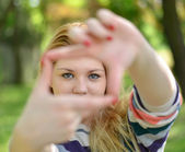 Beautiful girl making frame with hands while outdoors — Stock Photo