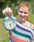 Teenage girl holding vontage clock outdoors with focus on clock — Stock Photo