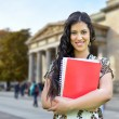 Portrait of happy student girl against street background — Stock Photo