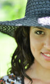 Half face shot of brunette girl with straw hat — Stock Photo