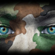 Soldier face with army colors looking from dark — Stock Photo
