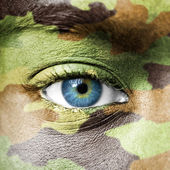 Soldier face with camo texture macro — Stock Photo