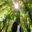 Young woman with arms raised enjoying the fresh air in green for — Stock Photo #25730853