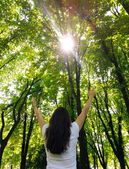 Young woman with arms raised enjoying the fresh air in green for — Stock Photo