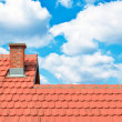 Brand new red rooftop against blue sky — Stock Photo #26498737