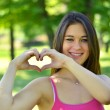 Cute teen girl making heart shape with her hands outdoors — ストック写真
