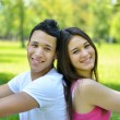 Foto Stock: Happy young couple back to back in park