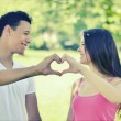 Retro image of couple making heart shape with hands in park — Stock Photo