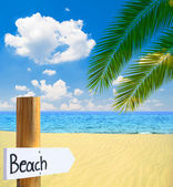 Paradise beach and sea with wooden board showing direction to th — Stock Photo