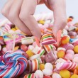 Hand grabbing candy from pile - Overweight problem concept — Stock Photo