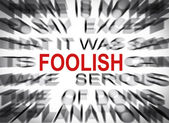 Blured text with focus on FOOLISH — Stockfoto