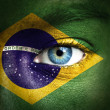 Human face painted with flag of Brazil — Stock Photo