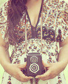 Retro image of woman hands holding vintage camera outdoors — Photo