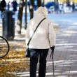 Foto Stock: Old lady walking with stick