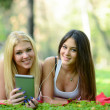 Happy teenage girls enjoying nature with tablet — Stock Photo