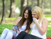 Two young women looking at tablet and chating online — ストック写真
