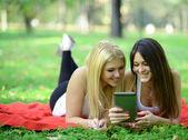 Teenage girls having fun online on digital tavblet outdoors in p — Stockfoto