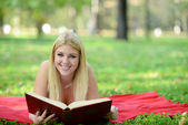 Happy smiling woman reading book in park — Stock Photo