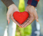 Hands of man and woman holding red heart — Stock Photo