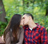 Couple kissing at the bench in park — Stock Photo