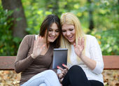 Friends chating with friend outdoor with digital tablet — Stock Photo