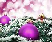 Purple christmas ornament ball against purple bokeh background — Stock Photo
