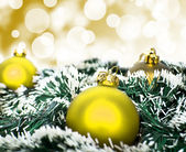 Yellow christmas ornament ball against yellow bokeh background — Stock Photo