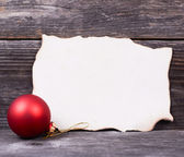 Christmas background with red bauble and blank paper — Stock Photo