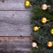 Christmas fir tree with golden decoration on a wooden board — Stock Photo