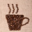 Coffee cup image made up of coffee beans on canvas background — Stock Photo