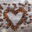 Stock Photo: Heart shape made from coffee beans on wooden background