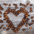 Heart shape made from coffee beans on wooden background — Stock Photo