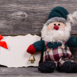 Santa Claus toy against wooden background with blank paper- Mess — Stock Photo