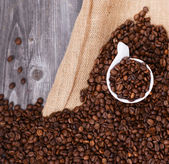 Cup of coffee filled with coffee beans against wooden background — Stock Photo