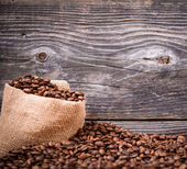 Sack of coffee beans on wood background — Stockfoto