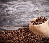 Sack of coffee grains against grunge wooden wall — Stock Photo